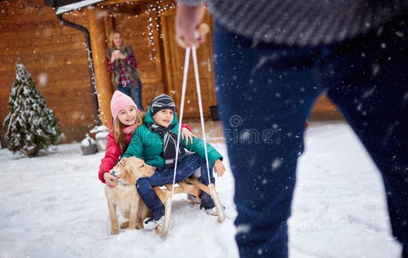 Enfants sur le traîneau dans le jour d'hiver avec le chien - vacances de famille image stock