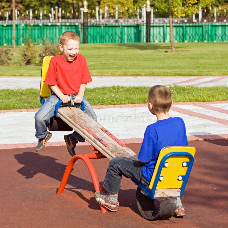 Enfants sur une balançoir photo libre de droits