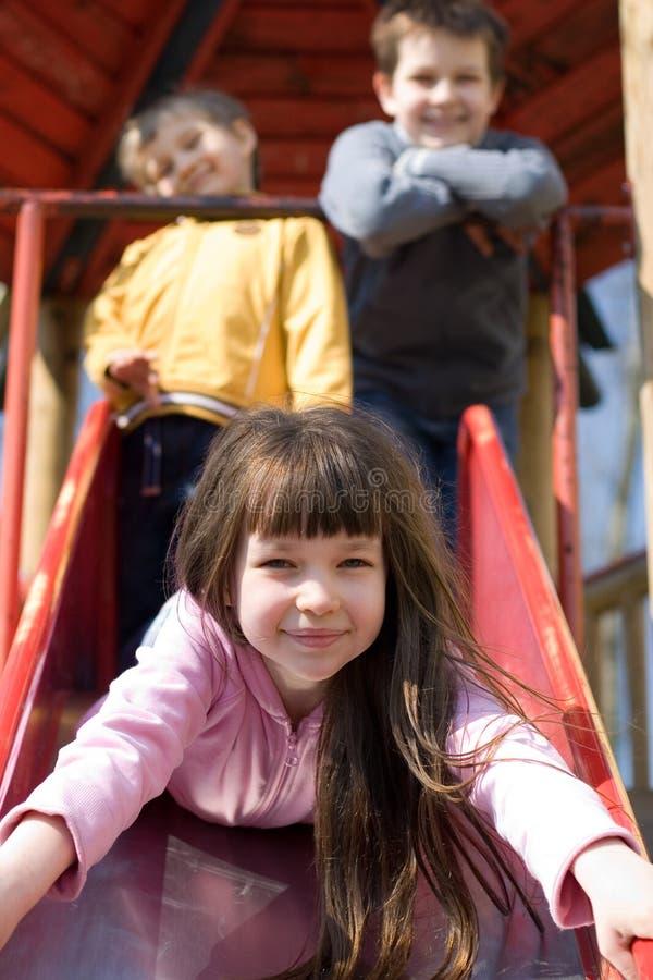 Enfants sur une cour de jeu photographie stock