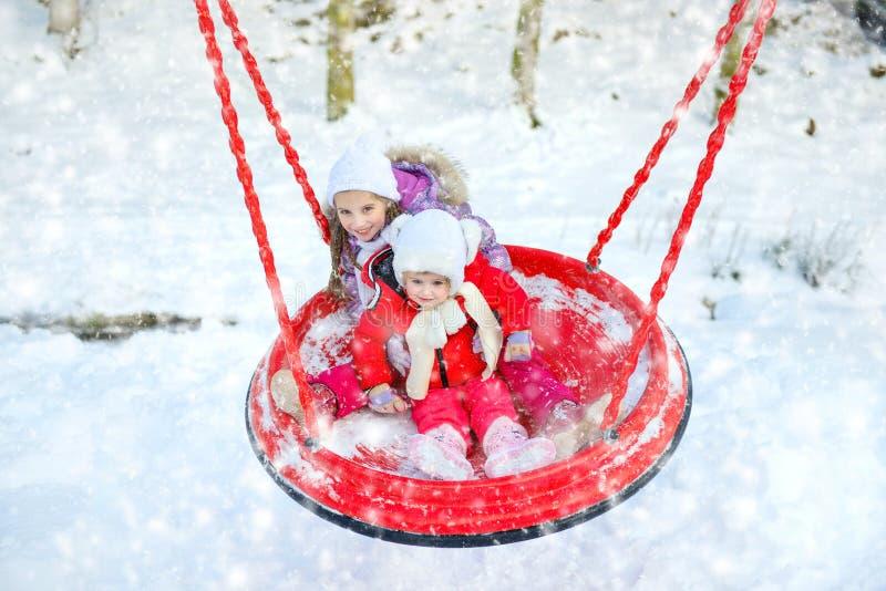 Enfants sur une oscillation en parc d'hiver photographie stock libre de droits