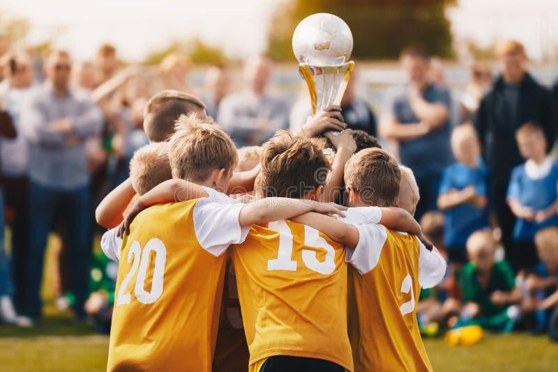 Enfants tenant la tasse d'or Garçons gagnant le championnat du football images stock