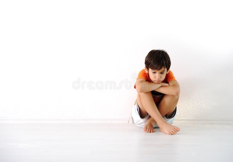 Enfants tristes s'asseyant à la maison photo libre de droits