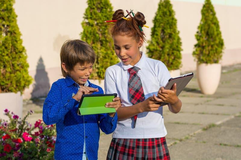 Enfants - un garçon et un support de fille avec des comprimés dans l'école yar image stock