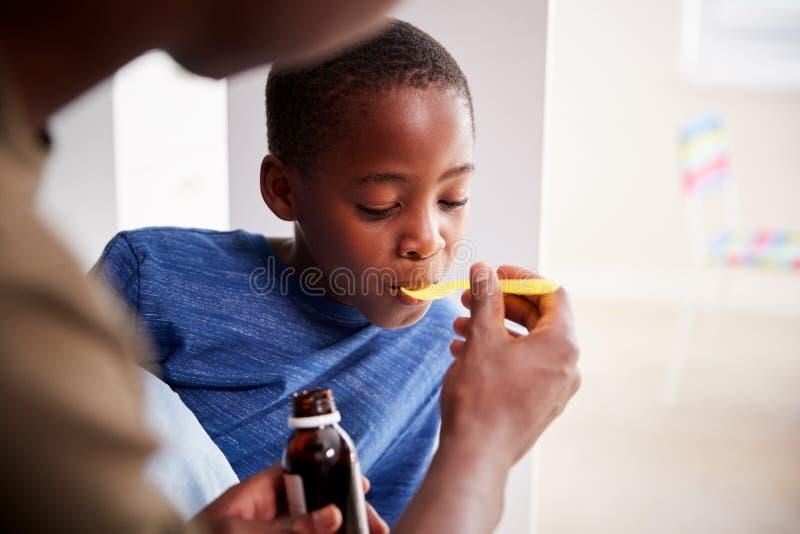 Enfermedad de Giving Sick Son del padre en medicina de la cama de la botella fotos de archivo libres de regalías