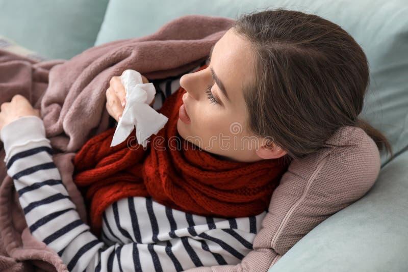 Enfermedad de la mujer joven con gripe en casa foto de archivo