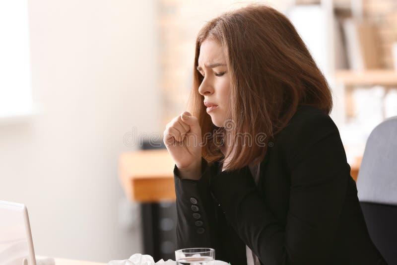 Enfermedad de la mujer joven con gripe en oficina foto de archivo