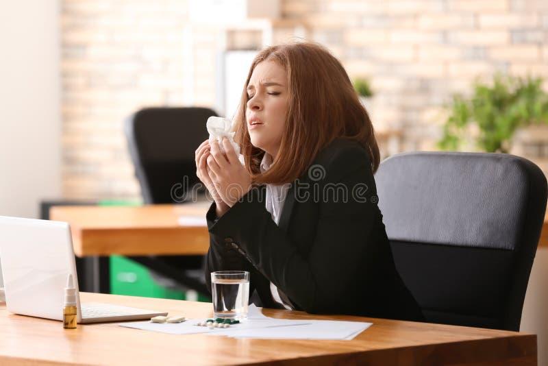 Enfermedad de la mujer joven con gripe en oficina imagen de archivo libre de regalías