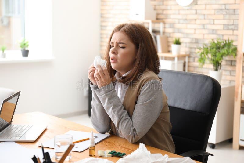 Enfermedad de la mujer joven con gripe en oficina fotografía de archivo