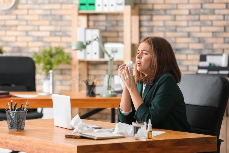 Enfermedad de la mujer joven con gripe en oficina imagen de archivo