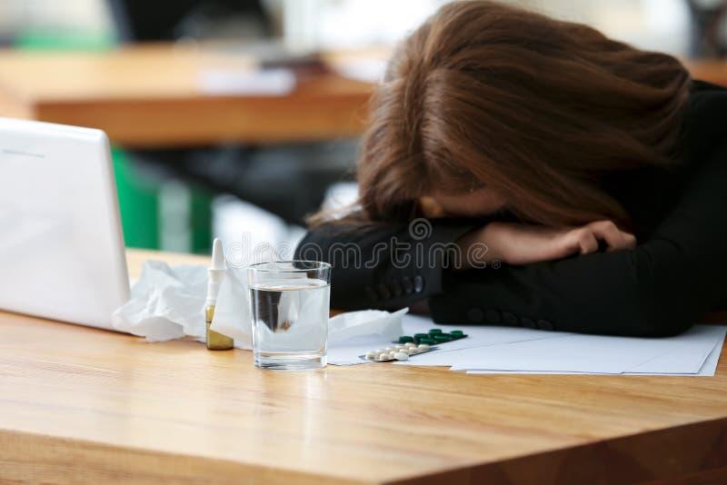 Enfermedad de la mujer joven con gripe en oficina fotos de archivo
