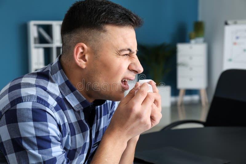 Enfermedad del hombre joven con gripe en oficina fotos de archivo