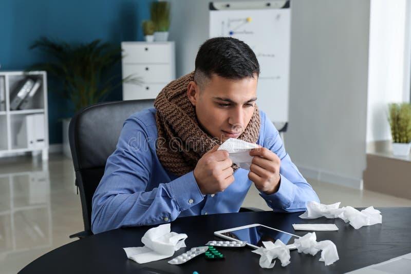 Enfermedad del hombre joven con gripe en oficina fotografía de archivo libre de regalías