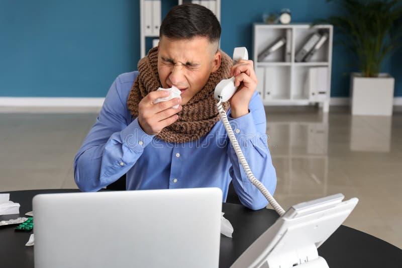 Enfermedad del hombre joven con gripe en oficina fotografía de archivo