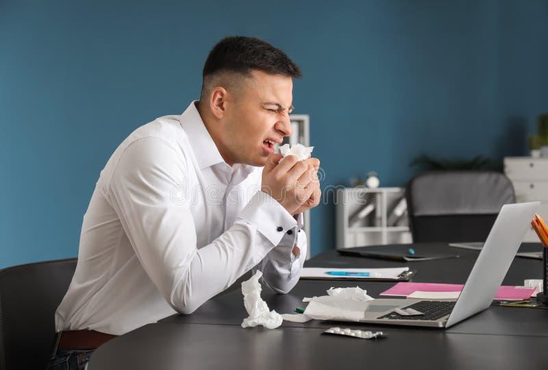 Enfermedad del hombre joven con gripe en oficina imágenes de archivo libres de regalías