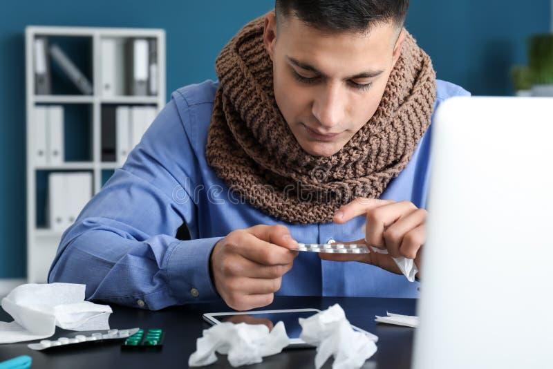 Enfermedad del hombre joven con gripe en oficina foto de archivo
