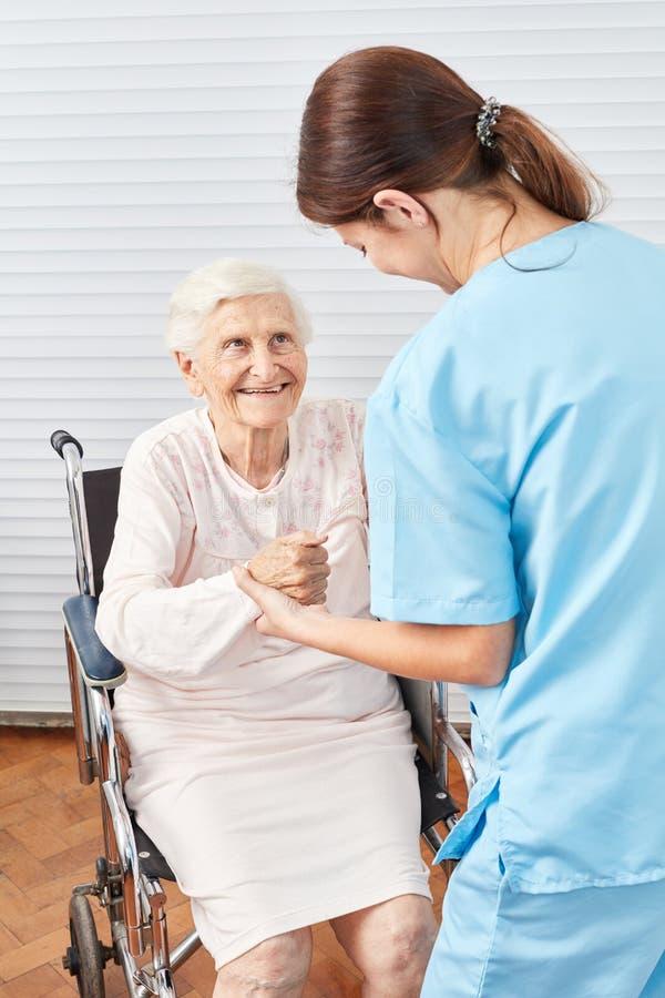 A enfermeira ajuda a mulher idosa frágil em uma cadeira de rodas fotografia de stock