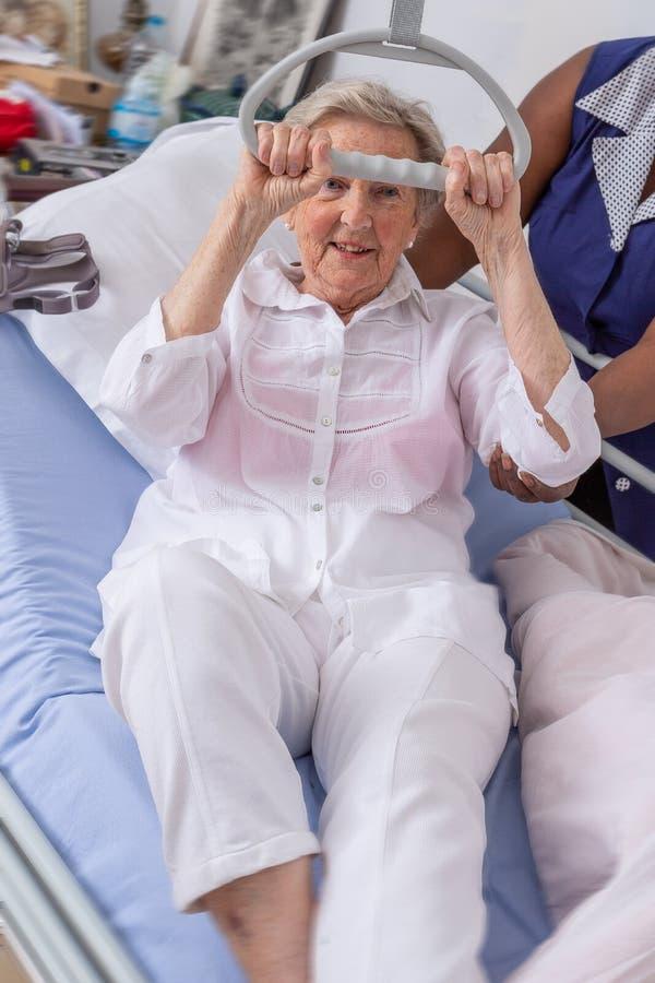 A enfermeira ajuda um paciente a levantar-se no hospital: enfermeira que ajuda a mulher superior a levantar-se com crédito fotos de stock royalty free