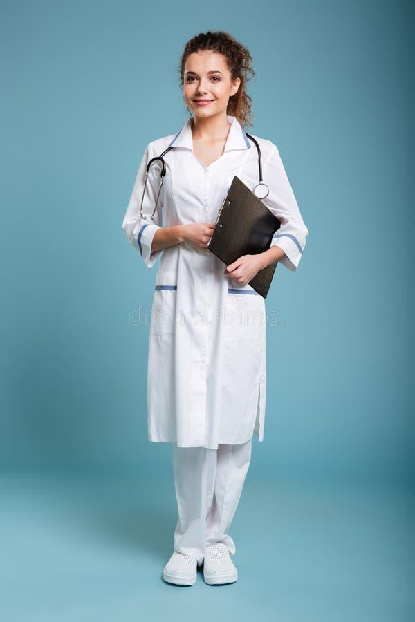 Enfermeira amigável de sorriso que guarda a prancheta e a vista da câmera fotografia de stock