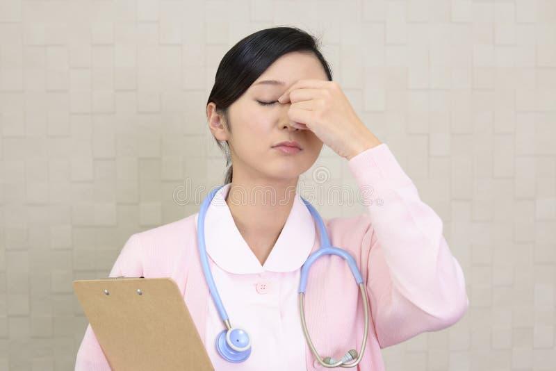 Enfermeira asiática cansado foto de stock