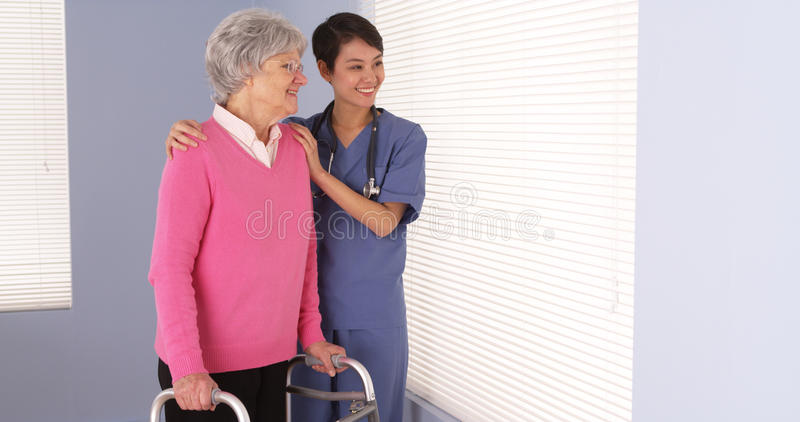 Enfermeira asiática e paciente idoso que estão pela janela imagens de stock