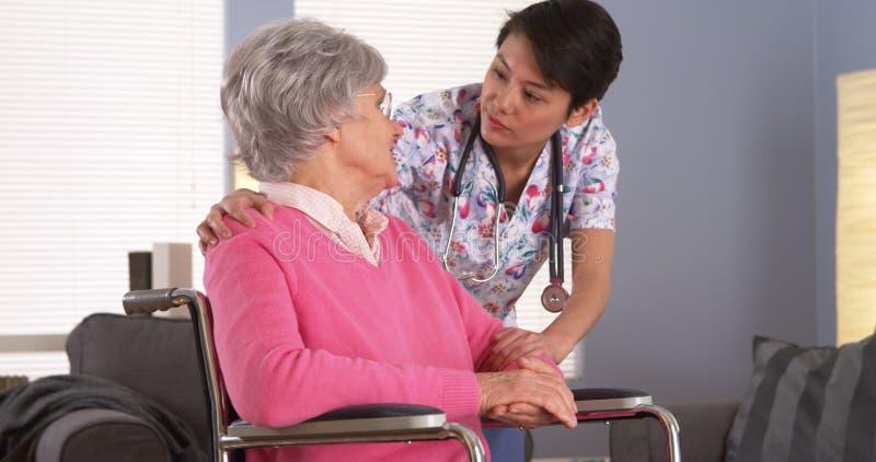 Enfermeira asiática que fala com paciente superior imagem de stock royalty free
