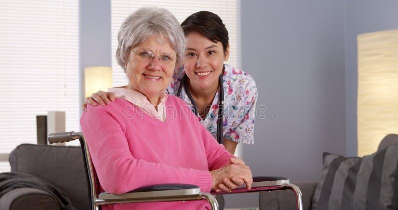 Enfermeira asiática que sorri com paciente idoso imagem de stock