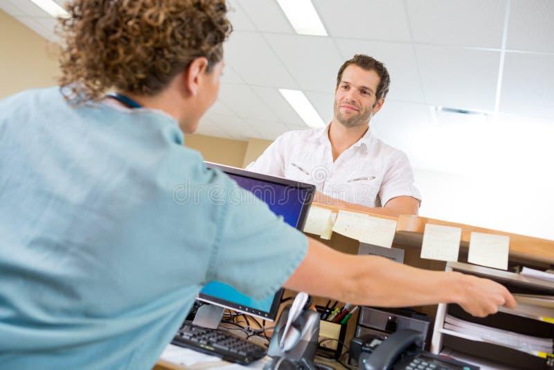 Enfermeira Assisting Man While que trabalha na recepção imagens de stock