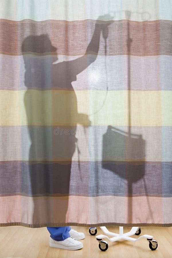Enfermeira atrás da cortina que prepara o gotejamento fotos de stock