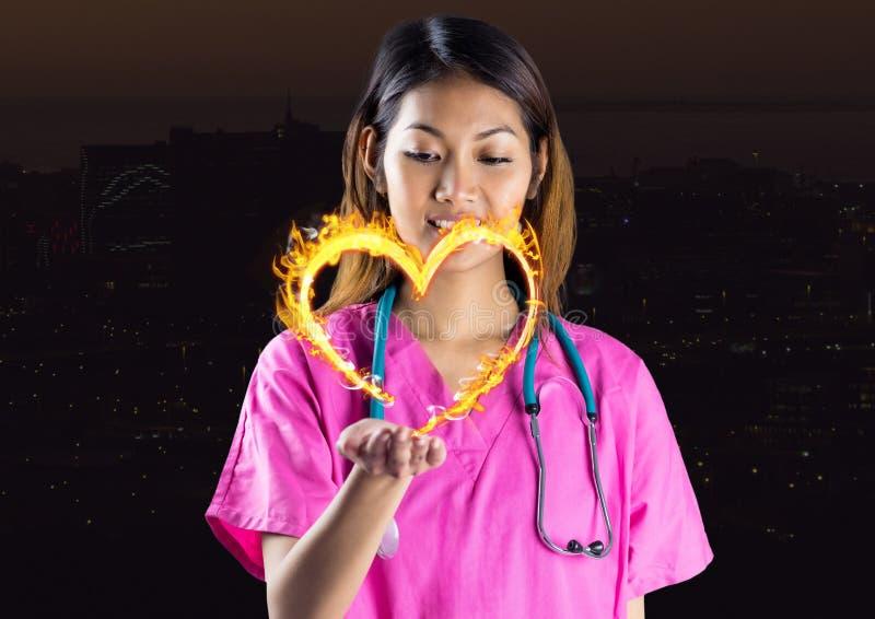 enfermeira com propagação da mão com do ícone do fogo do coração sobre na frente da cidade na noite imagens de stock royalty free