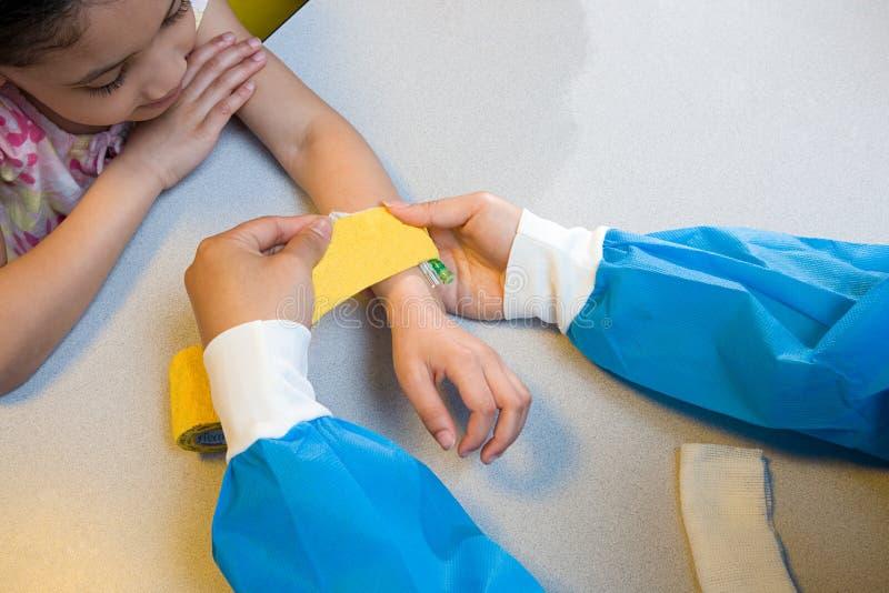 A enfermeira de observação da menina pôs a atadura sobre seu braço imagem de stock