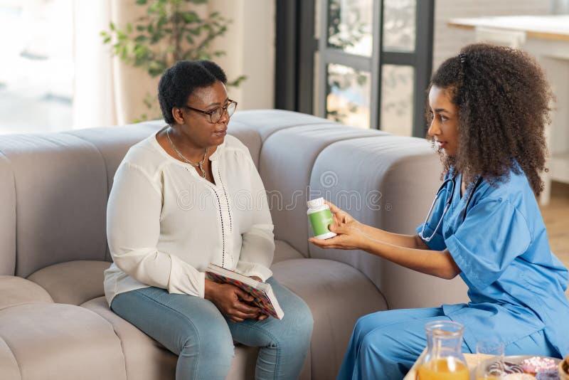 Enfermeira de pele escura encaracolado que dá o bloco com os comprimidos à mulher doente foto de stock royalty free