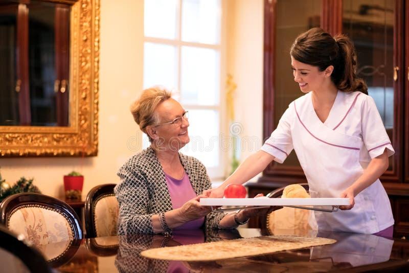 A enfermeira de sorriso dos jovens traz o café da manhã à mulher superior em cuidados imagens de stock
