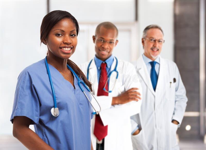 Enfermeira de sorriso na frente de sua equipa médica fotografia de stock royalty free