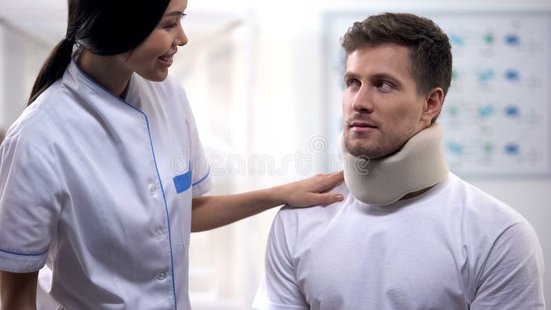Enfermeira de sorriso que olha o homem no colar cervical da espuma, cuidados médicos médicos, clínica fotos de stock royalty free