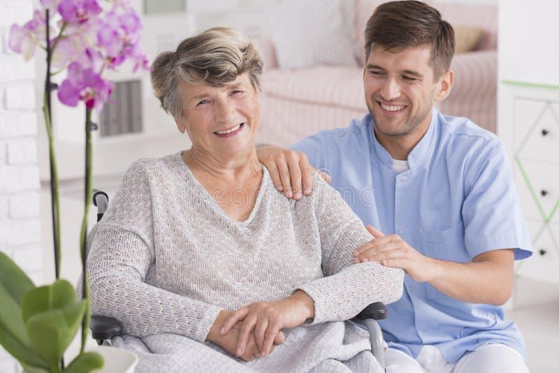 Enfermeira de sorriso que senta-se perto da mulher na cadeira de rodas fotos de stock royalty free