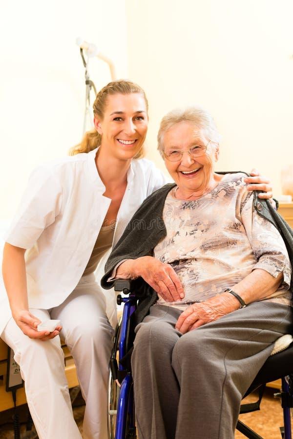 Enfermeira dos jovens e sênior fêmea no lar de idosos fotografia de stock