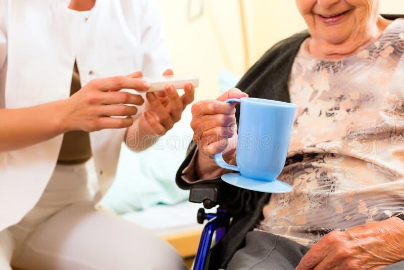 Enfermeira dos jovens e sênior fêmea no lar de idosos imagens de stock royalty free