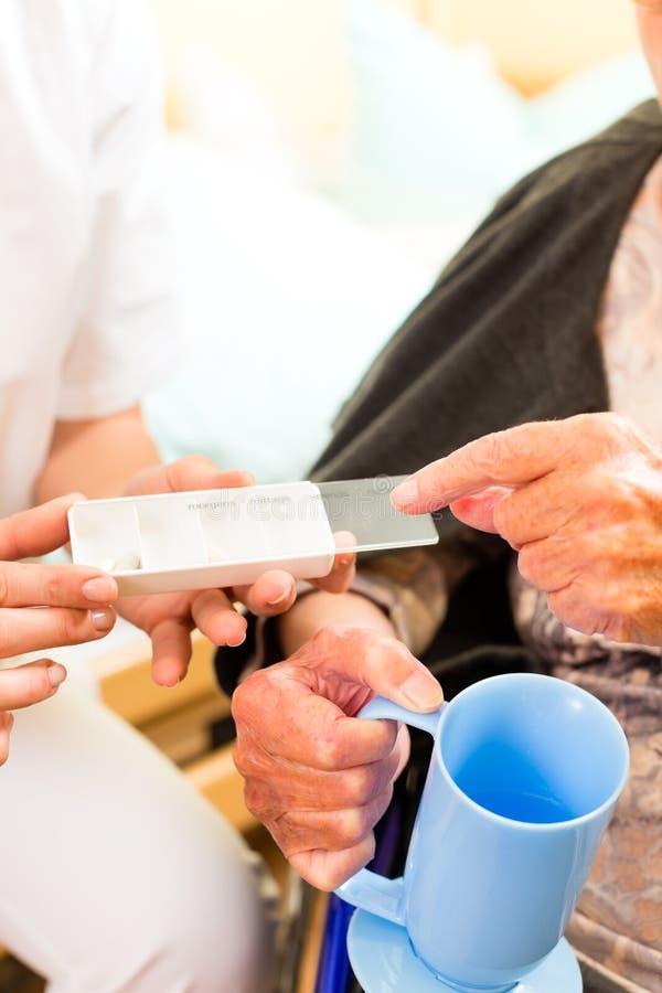 Enfermeira dos jovens e sênior fêmea no lar de idosos fotos de stock royalty free