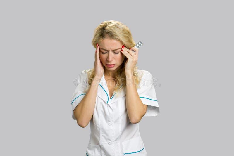 Enfermeira dos jovens que sofre da dor de cabeça fotografia de stock royalty free
