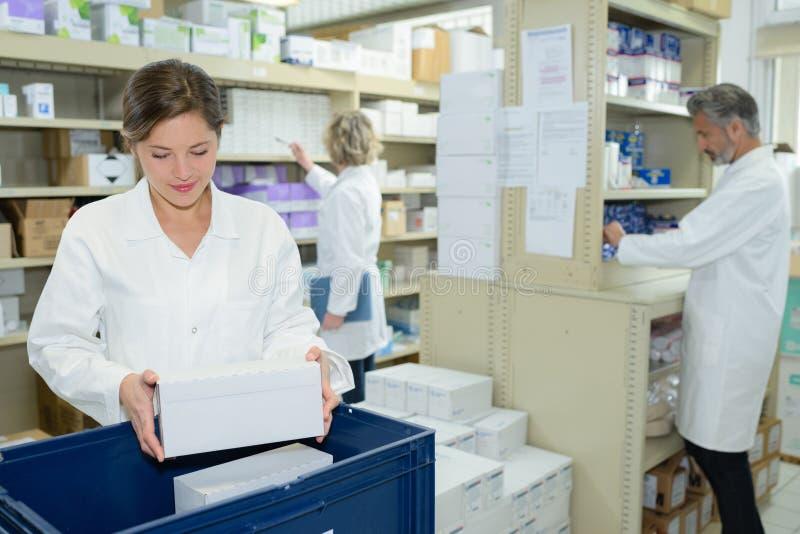 Enfermeira e farmacêuticos que trabalham na farmácia fotos de stock
