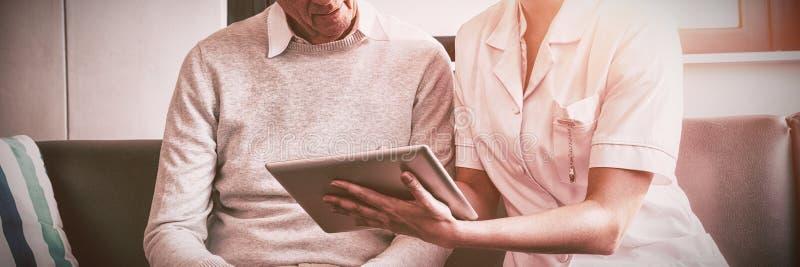 Enfermeira e homem superior que usa uma tabuleta digital fotografia de stock royalty free