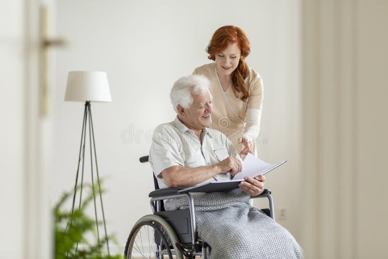 Enfermeira e paciente em uma cadeira de rodas que olha o álbum de fotografias junto e o sorriso imagens de stock