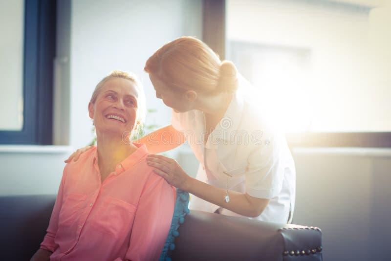 Enfermeira e paciente felizes na sala de visitas imagens de stock royalty free