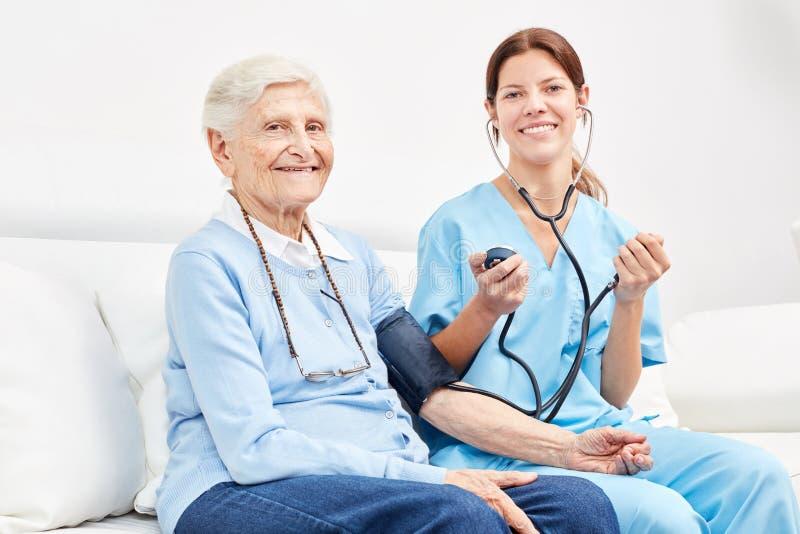 Enfermeira e sênior na medida da pressão sanguínea imagem de stock