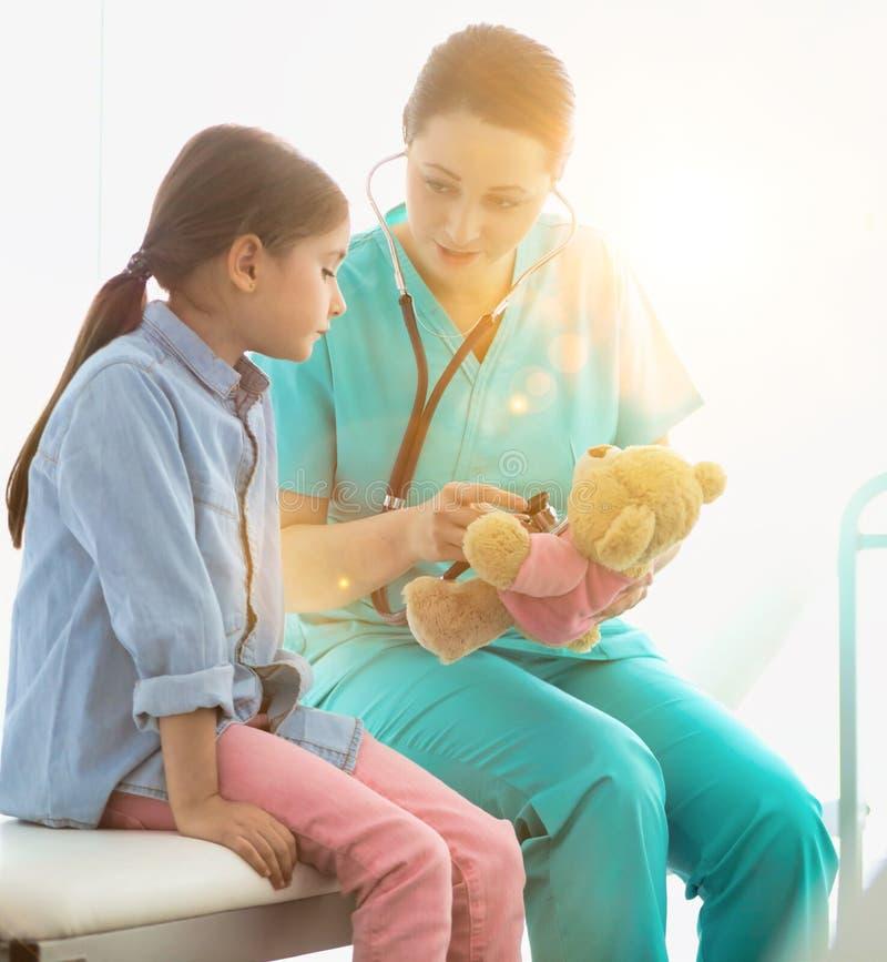 Enfermeira ensinando paciente infantil a verificar batimento cardíaco com ursinho no hospital imagem de stock