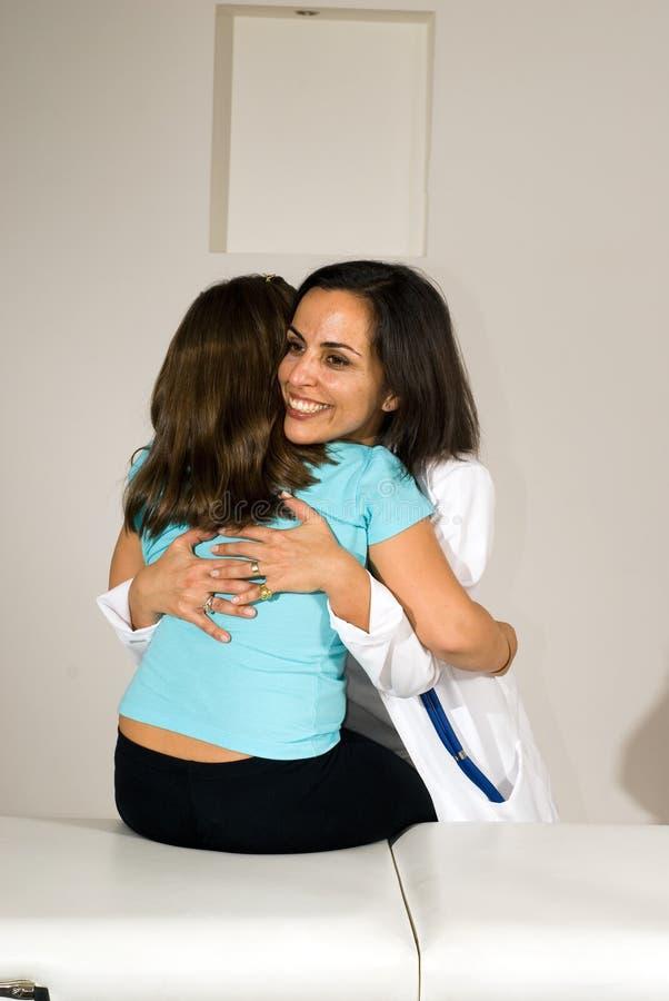Enfermeira ereta que abraça um paciente que senta-se na cama fotos de stock
