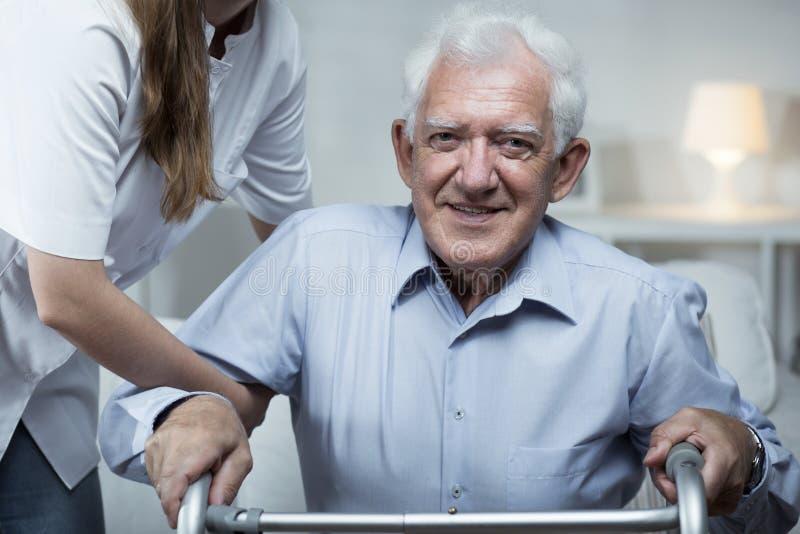 A enfermeira está ajudando um homem mais idoso foto de stock royalty free