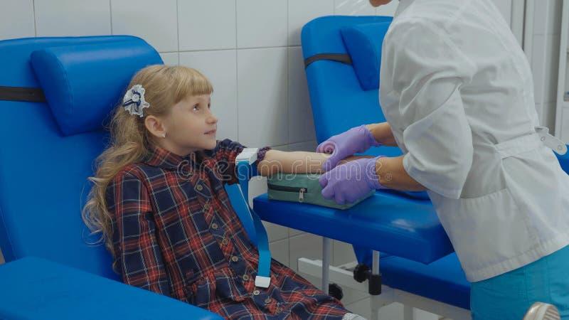 A enfermeira está tomando a amostra de sangue de uma veia no braço da menina imagens de stock royalty free