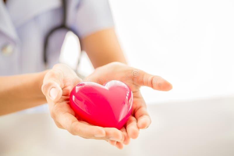 Enfermeira fêmea com o estetoscópio que guarda o coração fotografia de stock