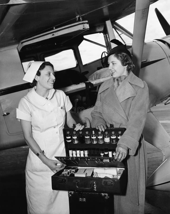 Enfermeira fêmea com uma jovem mulher que está na frente de um avião e que abre uma caixa da medicina (todas as pessoas descritas foto de stock royalty free